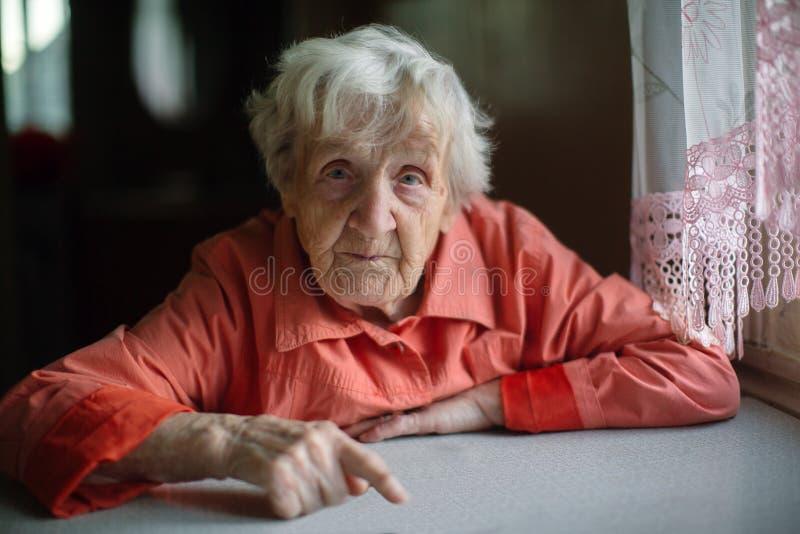 Samotny starszy damy obsiadanie blisko okno w kuchni obraz royalty free