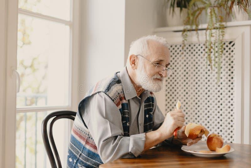 Samotny starszy mężczyzna jedzący jabłko przy stole w pustym domu zdjęcie stock