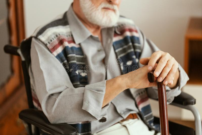 Samotny starszy mężczyzna siedzący na wózku inwalidzkim i trzymający laskę obrazy stock