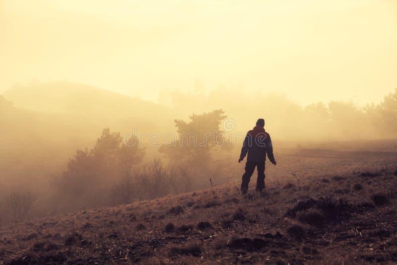 Samotny turysta iść przez mgła zmierzchu światła słonecznego przez halnego Demerdzhi obraz stock
