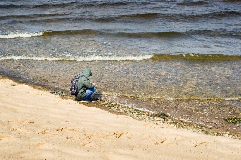 Samotny turysta na brzegu rzeki rzucający w wodę magnes poszukiwawczy fale rzeki biegnącej na brzeg zdjęcie royalty free