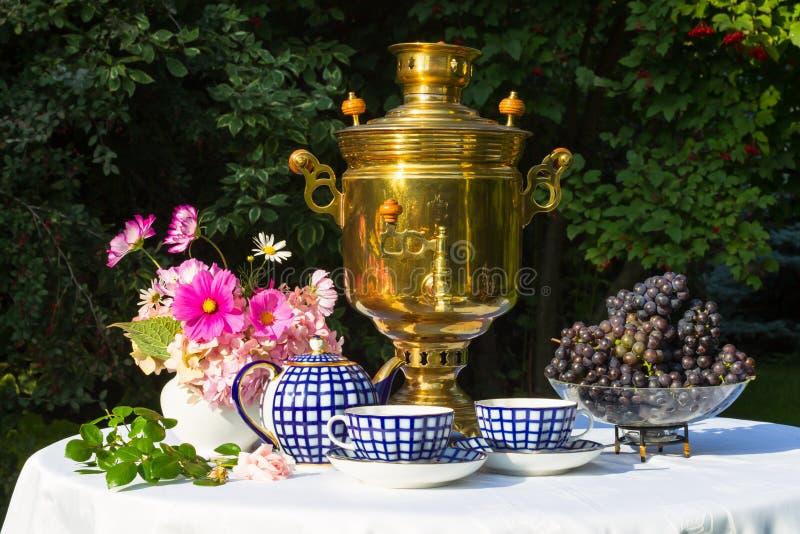 Samovar, copos do chá, flores cor-de-rosa e uvas em uma tabela coberta imagem de stock royalty free