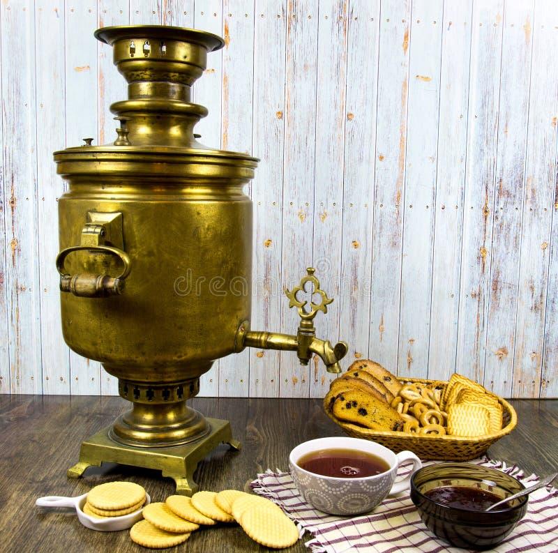 Samovar de cobre antiguo en una tabla de madera con una taza de atasco de las galletas de las migajas de pan del té imagen de archivo