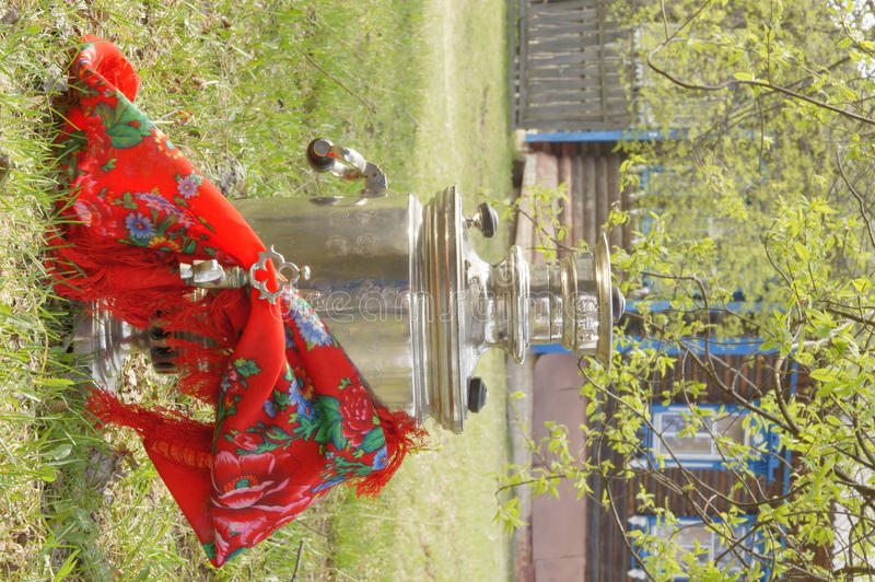Samovar with a handkerchief in the agricultural la. Russian kettle with the popular scarf is on the green grass on a background of a village house stock photography