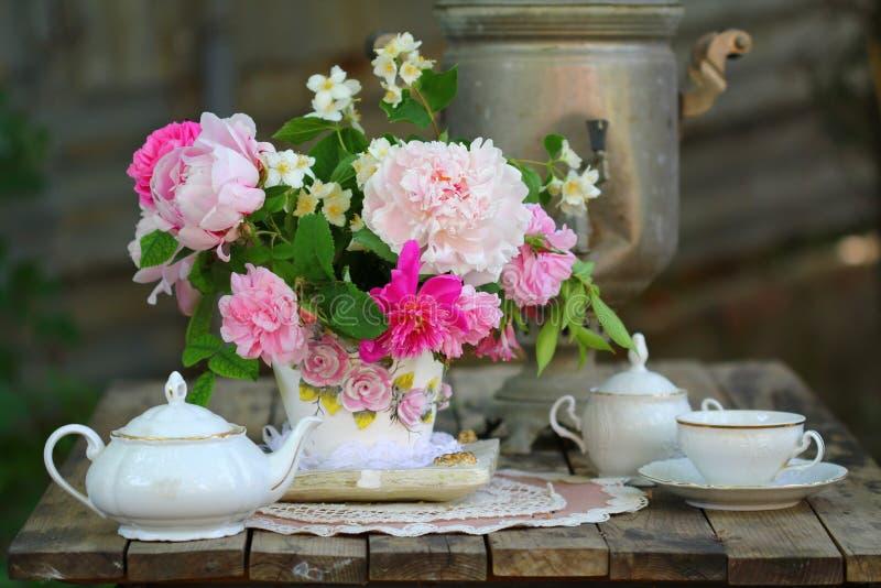 Samovar viejo ruso, tetera, taza y ramo hermoso de la primavera foto de archivo libre de regalías