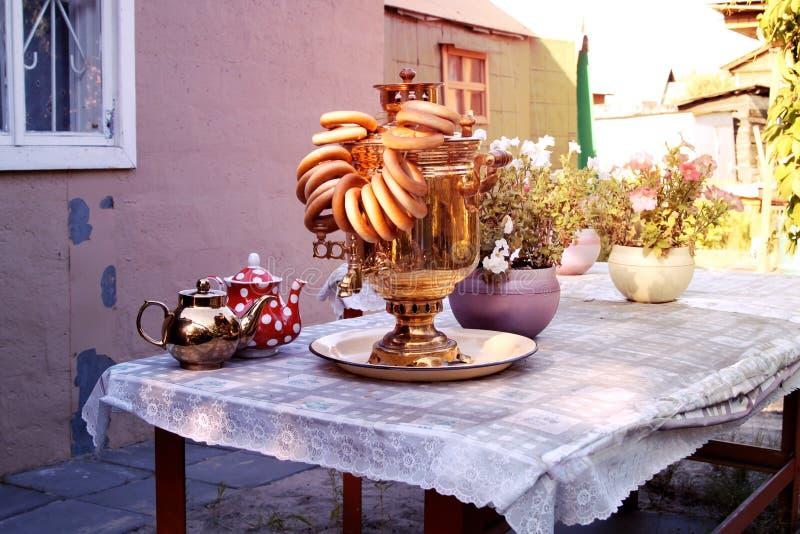 Samowar und Bagel auf Tabelle mit Leinentischdecke auf der Datscha lizenzfreie stockfotografie