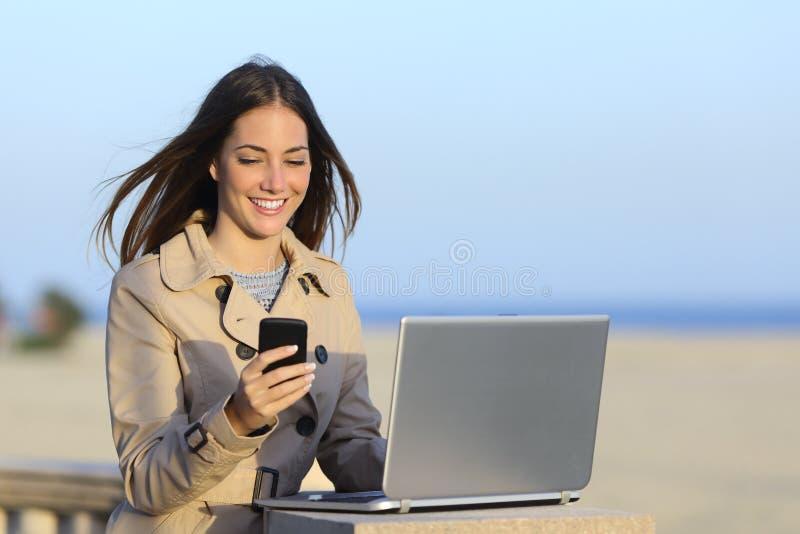Samozatrudniający się kobieta pracuje outdoors na telefonie obraz royalty free