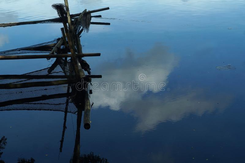 Rotting bamboo fish cage built along mountain lake shore stock image