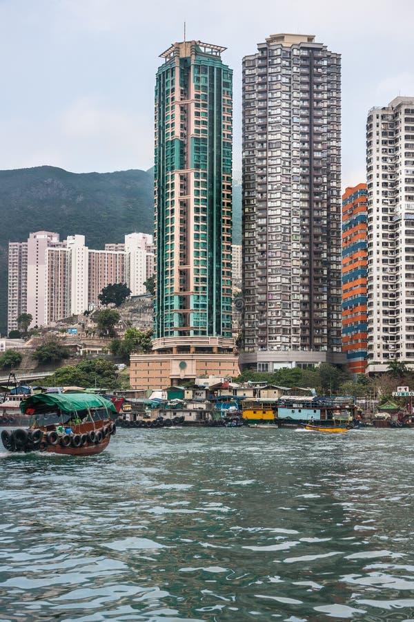 Sampan ferry in front of tall buildings in harbor of Hong Kong, China. Hong Kong, China - May 12, 2010: Brown wooden ferry sampan crosses the harbor with tall royalty free stock photos