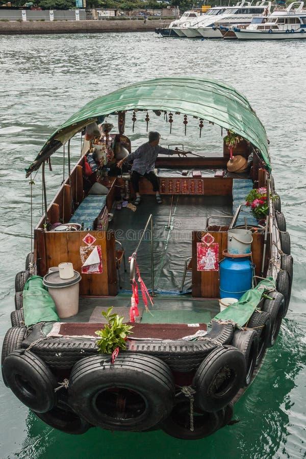 Sampan in Hong Kong Harbor, China. Hong Kong, China - May 12, 2010: Green roofed sampan tourist ferry docks in the harbor. White yachts in back. Greenish water stock photo
