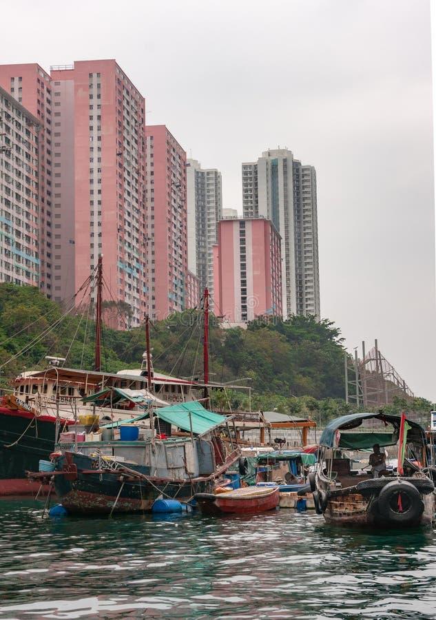 Sampans and houseboats docked in front of tall buildings in harbor of Hong Kong, China. Hong Kong, China - May 12, 2010: Brown wooden ferry sampan and group of royalty free stock images