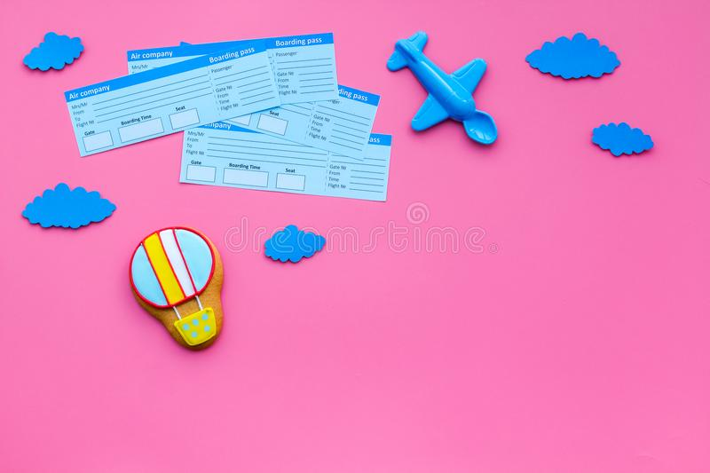 Sample of airplane ticket. Family trip with kid. Airplan, air balloon toys. Pink background flat lay space for text stock images