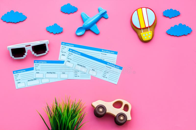Sample of airplane ticket. Family trip with kid. Airplan, car and air balloon toys. Pink background flat lay space for royalty free stock image