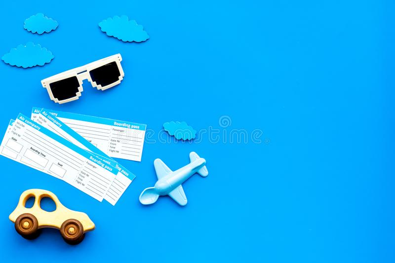 Sample of airplane ticket. Family trip with kid. Airplan, car toys. Blue background flat lay space for text stock photography