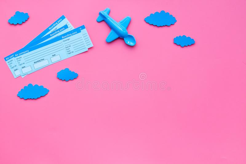 Sample of airplane ticket. Family trip with kid. Airplan toy and paper clouds. Pink background flat lay space for text stock images