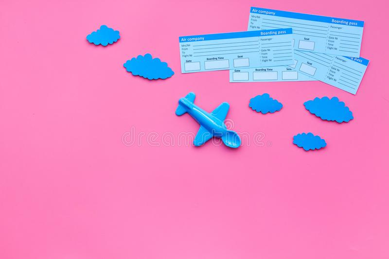 Sample of airplane ticket. Family trip with kid. Airplan toy and paper clouds. Pink background flat lay space for text stock image