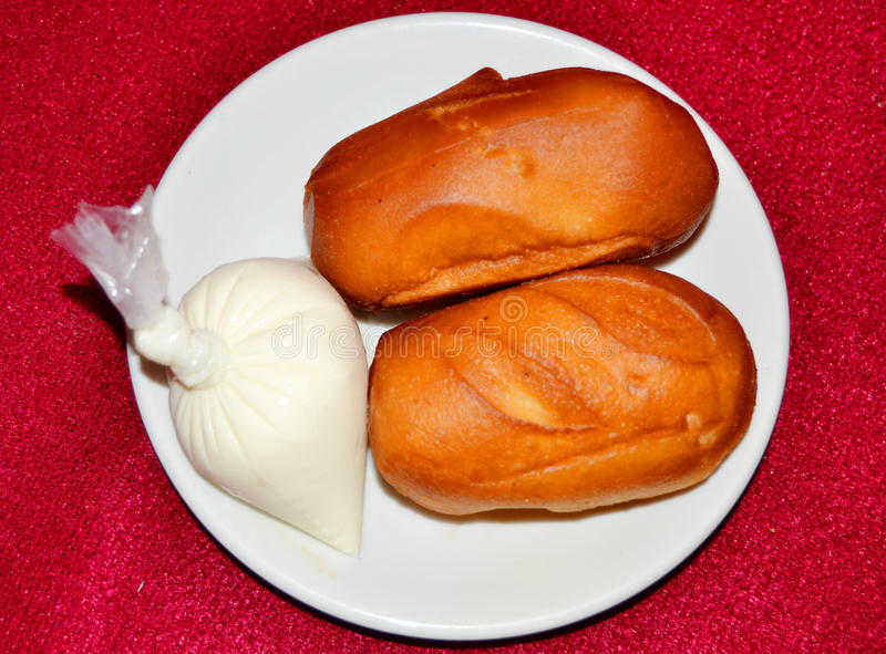 SAMPLE OF BEIGNET OF FLOUR. Sample of sweet dishes in a dish on a red background made of a fairly fluid paste, which is fried in oil accompanied with milk giving stock image