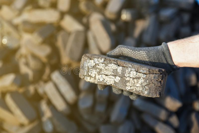 Sample of peat briquette in hand, alternative fuels. Raw material stock photos