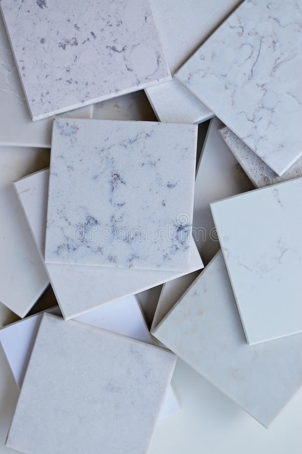 Samples of different stones mainly white based with marble like grains and veins. Samples of different stones in square shape stacked on top of each other in royalty free stock photos