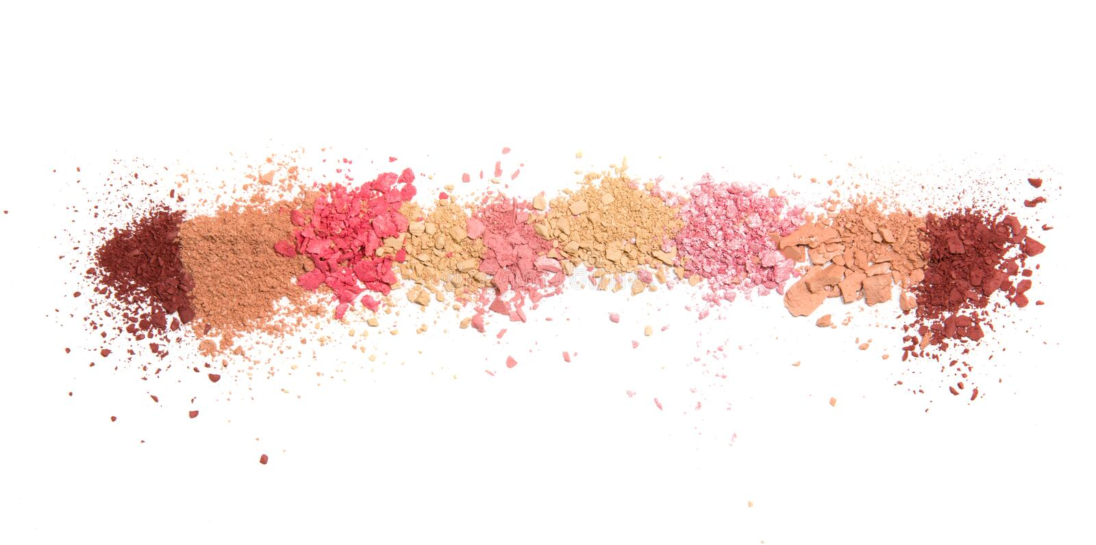 Samples of dry blush, powder, bronzers and highlighter scattered in a line isolated on a white background royalty free stock photos
