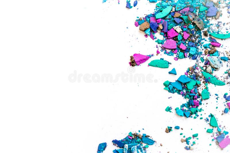 Makeup trends. Samples of dry blush, powder, bronzers and highlighter scattered on a white background. purple, blue, gray broken o. Samples of dry blush, powder stock images