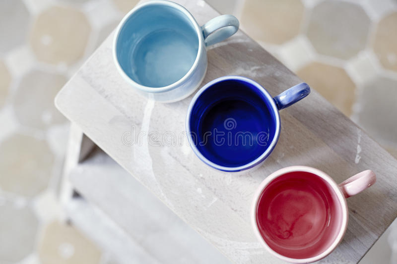 Samples handmade ceramic colored cups on wooden table, working process in studio. Samples handmade ceramic colored cups on wooden table, working process in stock photography
