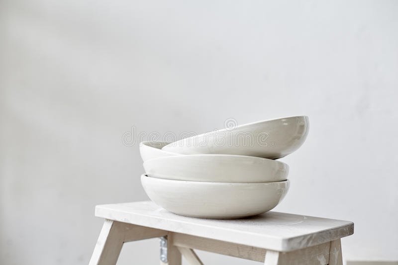 Samples handmade ceramic white plates on wooden table, working process in studio.  stock photography