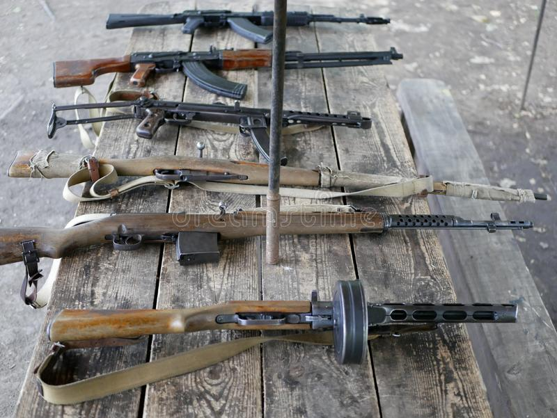 Samples of Soviet automatic weapons of the second world war. Machine guns and machine guns on a wooden table outside on a summer d. Ay royalty free stock photos