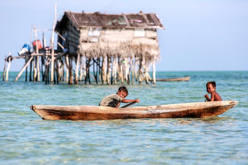 Samporna Sabah, Malásia, fevereiro 29,2016: As crianças desconhecidas usam sua canoa como o transporte principal na ilha de Maiga imagem de stock royalty free