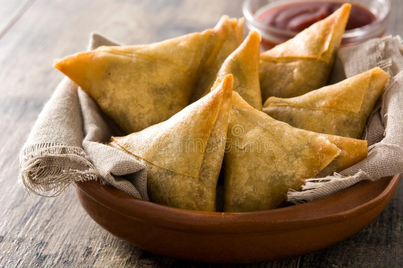 Samsa or samosas with meat and vegetables on wooden table. Traditional Indian food. Samsa or samosas with meat and vegetables in bowl on wooden table stock photos