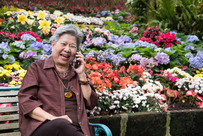 samtal för äldre kvinna på mobiltelefonen i trädgård den äldre kvinnlign talar arkivfoto