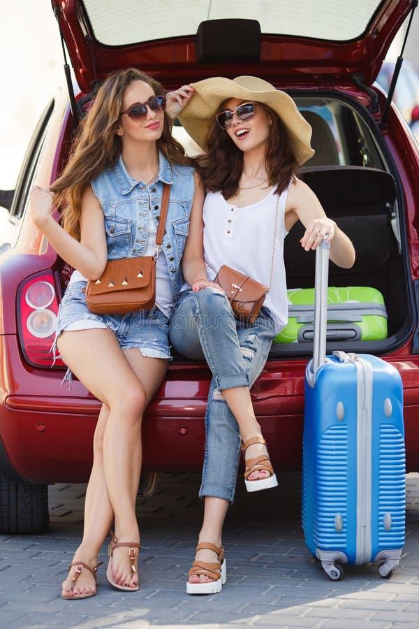 Samtal för två flickvänner som sitter i öppen bilstam royaltyfria foton
