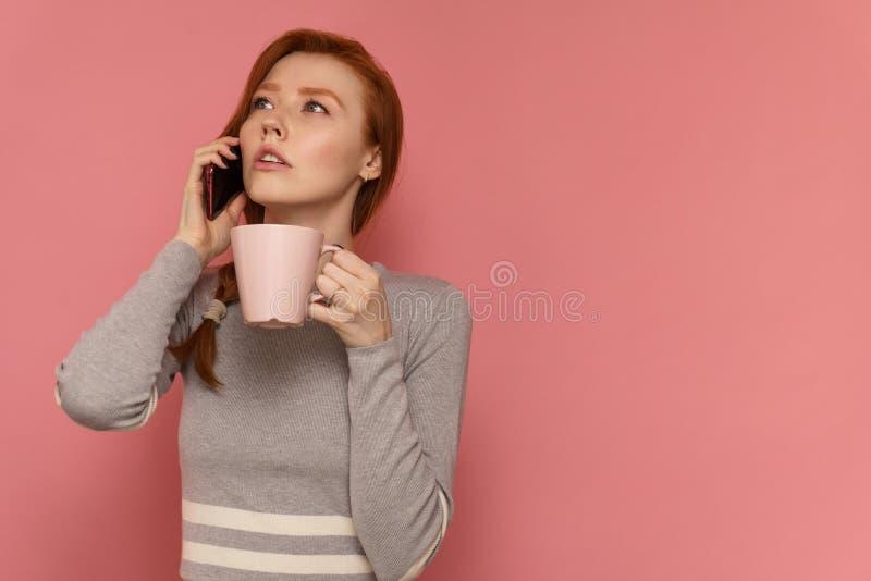 Samtal för ung kvinna för rödhårig man på telefonen som rymmer en kopp i på en hand som bort ser royaltyfri fotografi