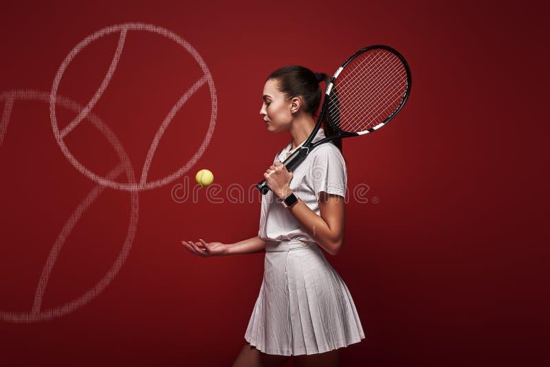 Samtal med din raquet, lek med din hjärta Ungt tennisspelareanseende som isoleras över röd bakgrund med en racket och fotografering för bildbyråer
