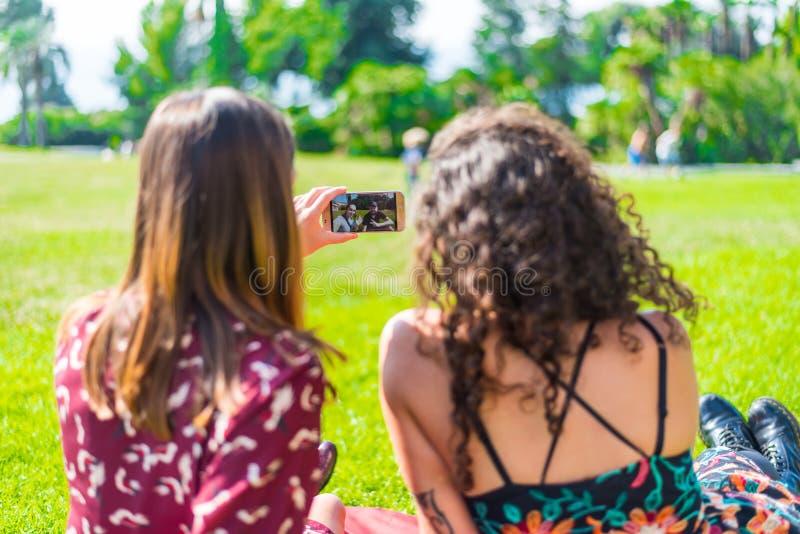 Samtal med vänner i parkerar royaltyfri bild
