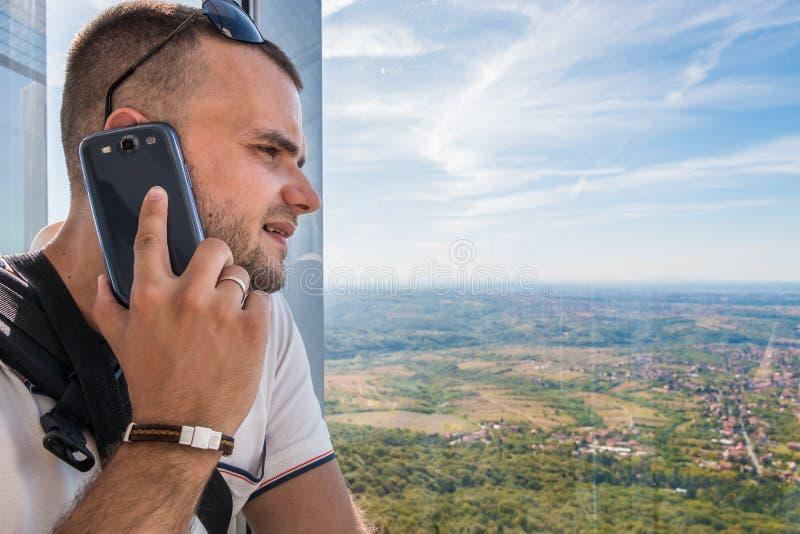 Samtal på telefonen och tycka om berglandskap arkivbilder