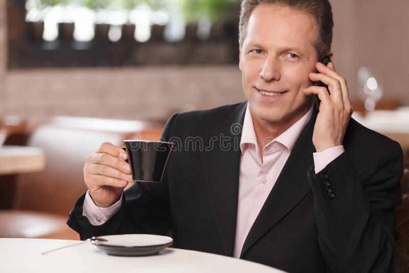 Samtal till affärspartnern. Gladlynt affärsman som dricker coffe arkivbild