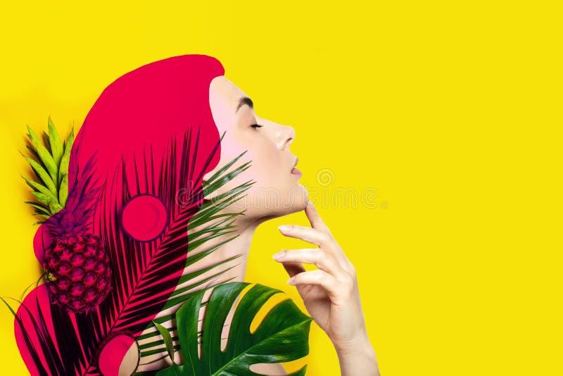 Samtida konstcollage av den härliga kvinnan med tropiska frukter och palmblad på gul bakgrund royaltyfri bild