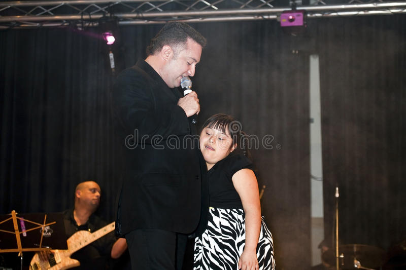 Samuel Hernandez performing during a Christian concert in the Br. BRONX, NEW YORK - MARCH 17: Samuel Hernandez performs while holding a down syndrome child stock photos