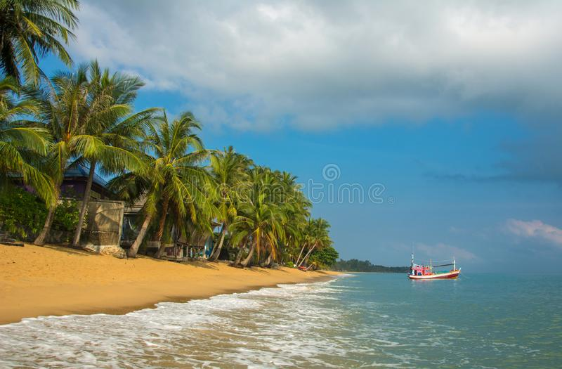 Samui MaeNam morning beach with coconut palms under sky, idyllic landscape. Samui MaeNam morning beach with coconut palms and fisherman\'s boat under blue sky stock images