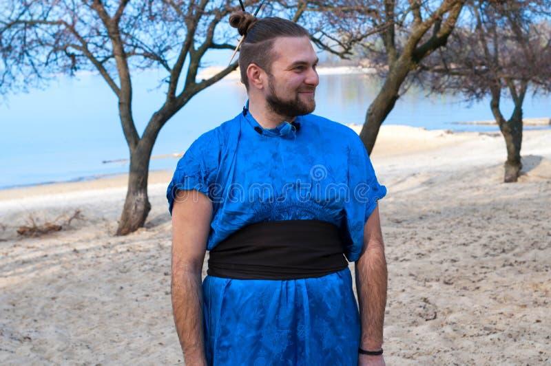 Samurai barbuto di peso eccessivo in kimono blu, panino e bastoni sulla testa che sta, distogliere lo sguardo e ridere fotografie stock libere da diritti