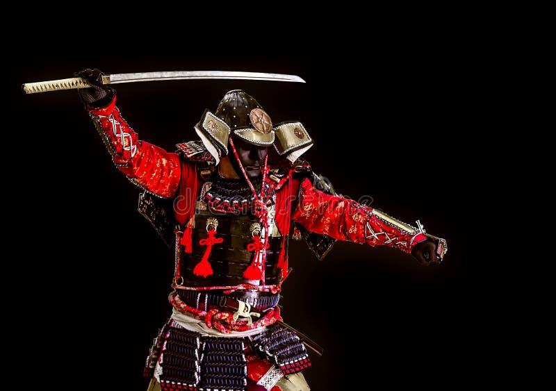 Samurai en armadura antigua con un ataque de la espada fotos de archivo
