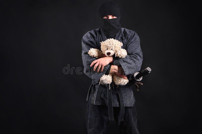 Samurai grande y potente del ninja que sostiene un oso de peluche fotografía de archivo