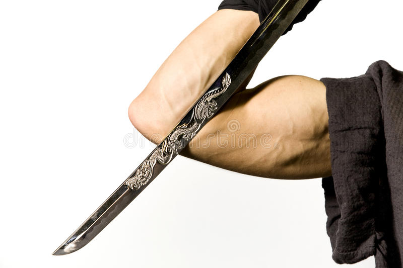 Samurai sword and strong arm. The strong arm of a martial artist holding a katana or samurai sword symbolically against a white background stock photography