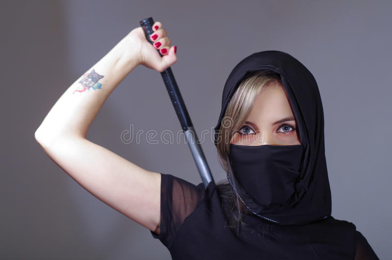 Samurai woman dressed in black with matching veil covering face, holding arm on sword hidden behind back, facing camera royalty free stock photography