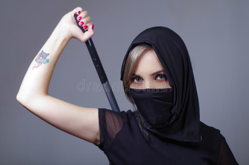 Samurai woman dressed in black with matching veil covering face, holding arm on sword hidden behind back, facing camera stock photo