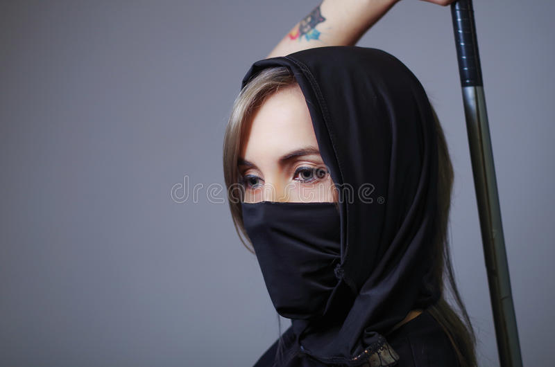 Samurai woman dressed in black with matching veil covering face, holding arm on sword hidden behind back, facing camera stock image