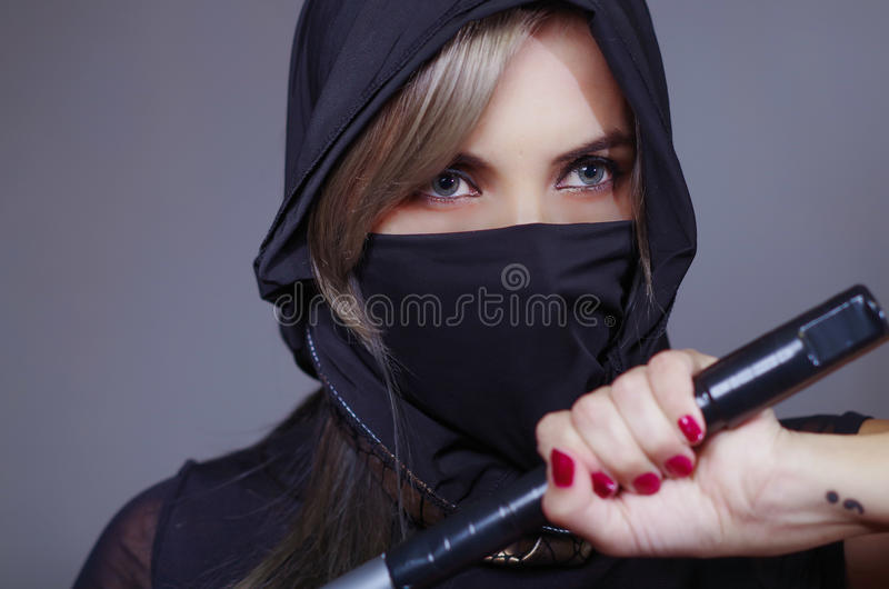 Samurai woman dressed in black with matching veil covering face, holding hand on sword facing camera, ninja concept royalty free stock image