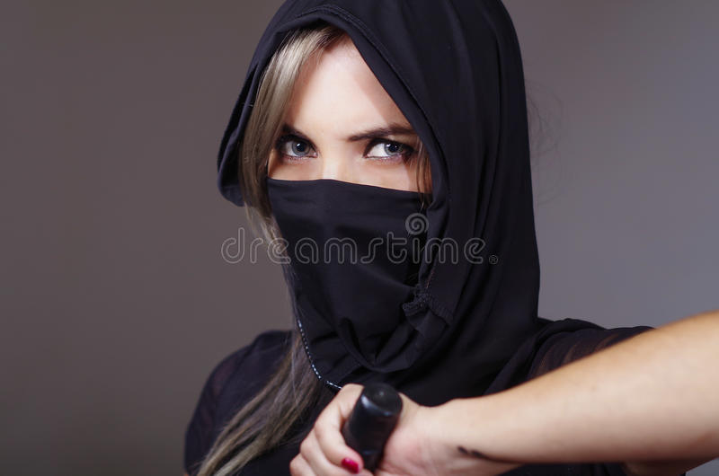 Samurai woman dressed in black with matching veil covering face, holding hand on sword facing camera, ninja concept.  stock image