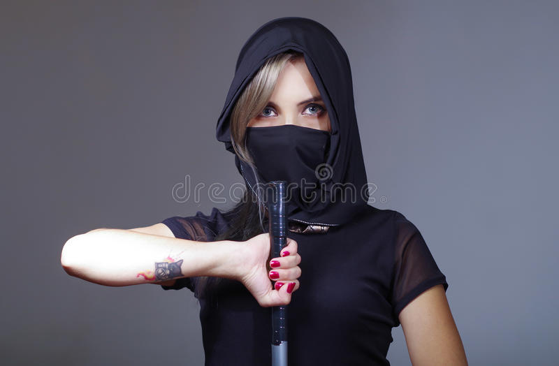 Samurai woman dressed in black with matching veil covering face, holding hand on sword facing camera, ninja concept.  royalty free stock photo